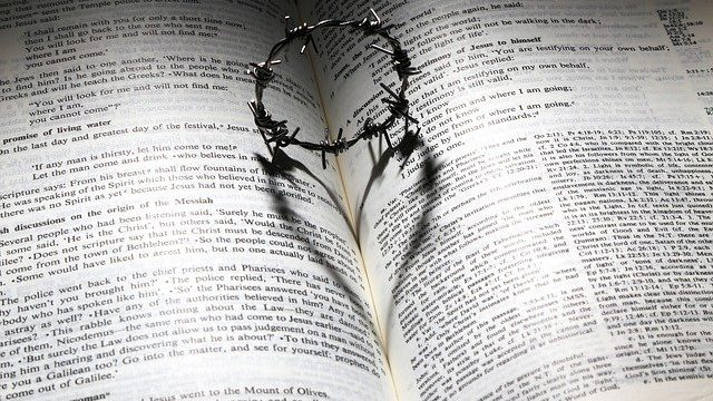 A barbed wire crown resting on a Bible casts the shadow of a heart on the Bible
