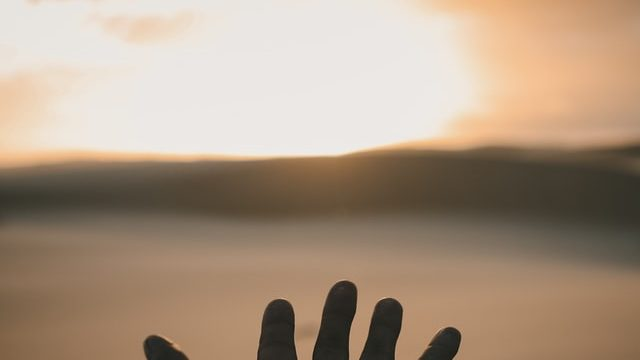 a upturned hand reaches into the distance in welcome