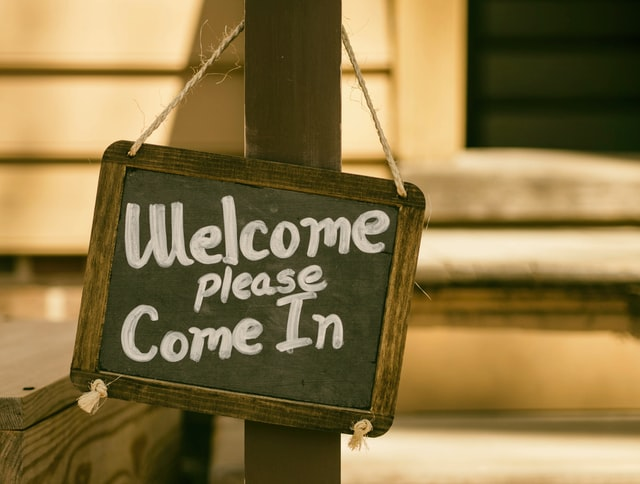 "a chalk sign saying ""Welcome. Please Come In"""