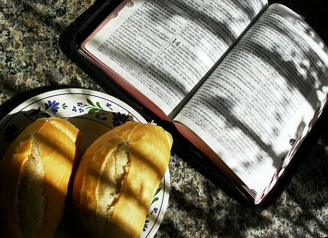 an open bible as spiritual nourishment alongside two small loaves of bread for physical nourishment