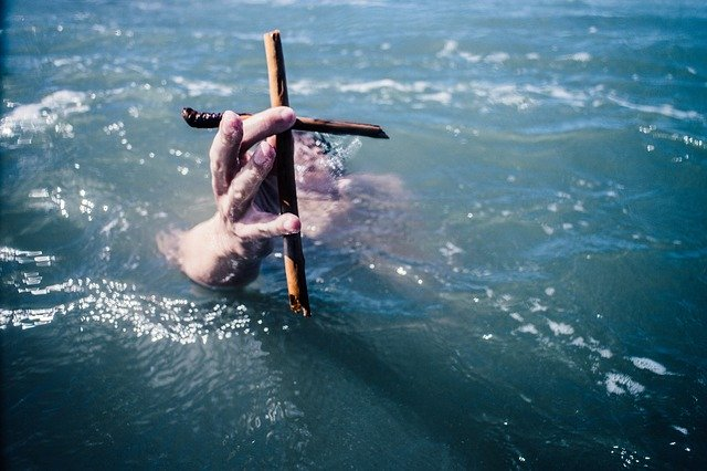 A hand emerging from the ocean holding a cross