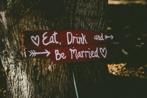 "A wooden sign on a tree with the text ""Eat, Drink and Be Married"""